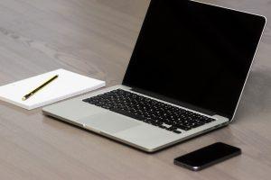 Slika prenosnika, mobilnega telefona, svinčnika in bloka za pisanje