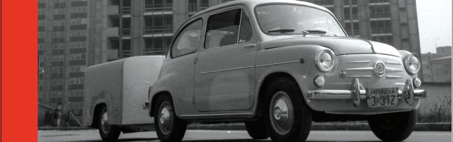 """Črnobel slika. Stari avtomobil znamke fiat 500 """"fičko"""" s prikolico."""